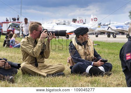 Men In Vintage Pilot Uniforms Taking Pictures With Cameras With The Swiss Pilatus Warbird Aerobatic
