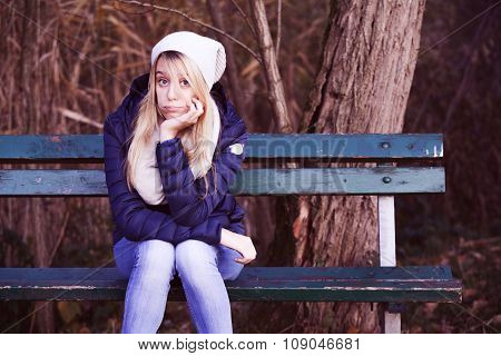 young blonde  bored girl on a bench