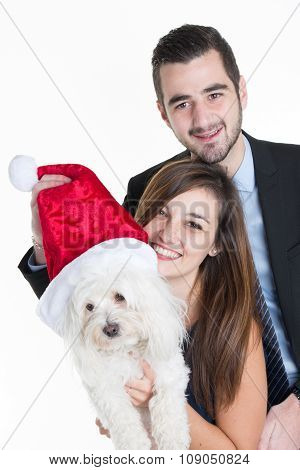 Studio Shot Of A Young Couple And Their Dog Wearing Santa Hats