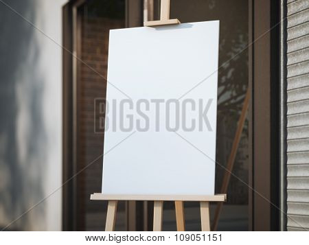 Wooden easel with a white canvas on the street