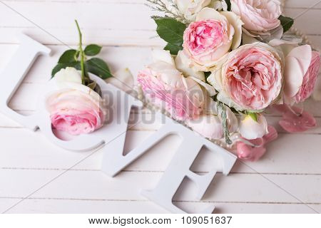 Sweet Pink Roses Flowers  And Word Love On White Painted Wooden Background.