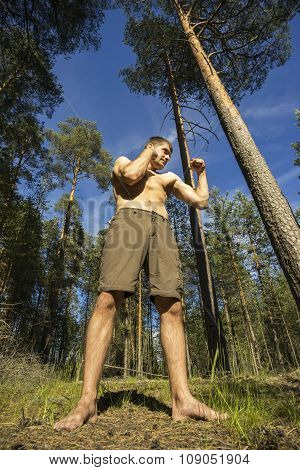 Young Man Stands In  Forest On The Pose Of A Boxer.