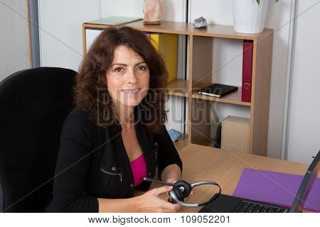 Portrait Of A Woman Sat At A Desk With A Headphone In Hands