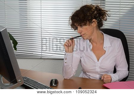 Thoughtful Businesswoman Sitting At Desk Looking At Computer In Her Office