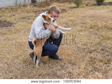 Boy and Basenji dog playing in autumanl garden