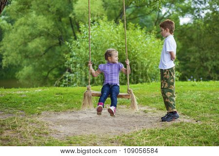 Little girl and boy on a swing in the summer park