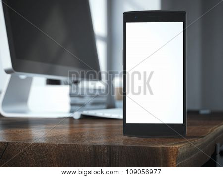 Modern smart phone with blank screen on the wooden table.