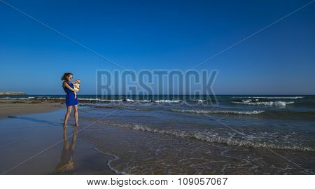 Mother With Baby On The Sea Beach