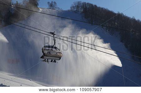 Ski Lift Gondola Against Automized Artificial Snow