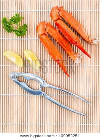 Boiled Crab Claws With Lime And Parsley On Bamboo Background.