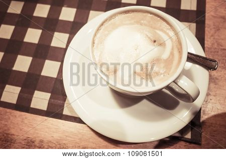 White Cup Of Cappuccino Stands On Wooden Table