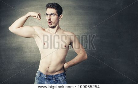 Shirtless male model posing with glasses over a gray background with muscles
