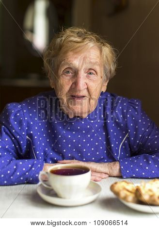 Portrait of an old granny drinks black tea at the table.