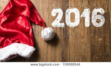 2016 written on wooden with Santa Hat