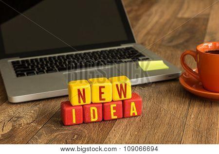 New Idea written on a wooden cube in a office desk