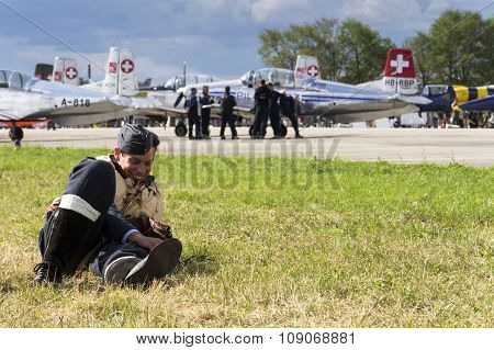 Man In Vintage Pilot Uniform Smiling With The Swiss Pilatus Aerobatic Team P3 Flyers In Background