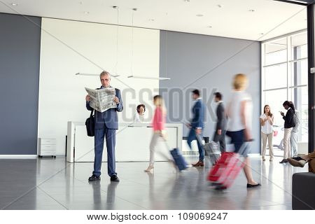 Elegant businessman read newspaper at airport