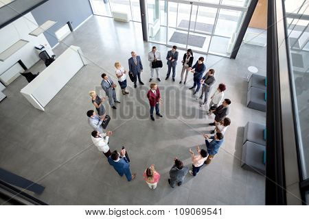 Top view of satisfied team clapping hands with manager in center of circle