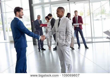 Young workman at entrance welcome black man passenger