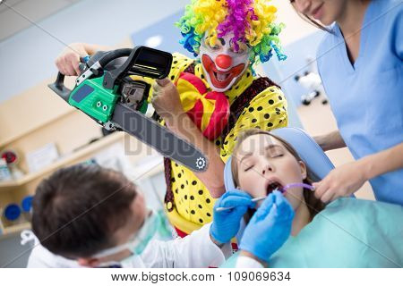 Crazy clown from horror threatens girl with chainsaw in dental clinic