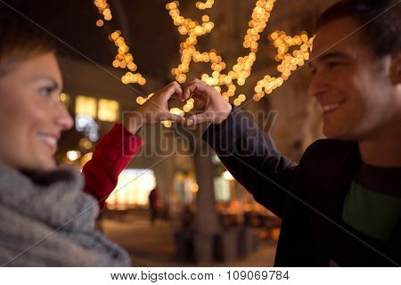 laughing happy lovers  making heart shape by their hands with Christmas light in background