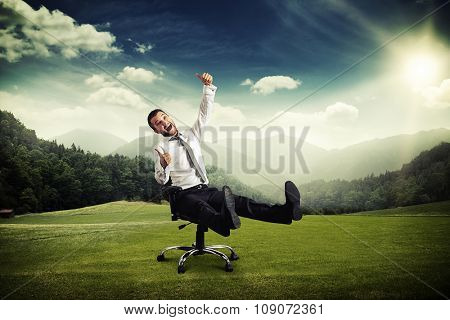 happy screaming businessman sitting on chair and showing thumbs up at outdoor