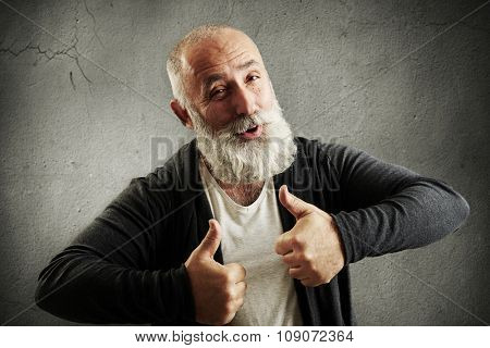 laughing bearded man showing thumbs up and looking at camera over grey wall