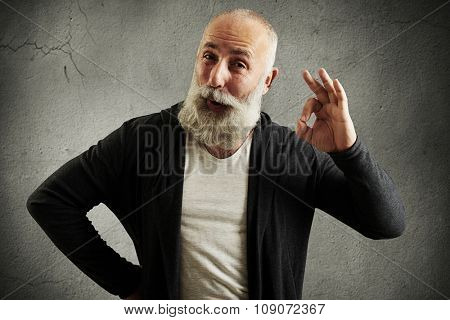 bearded senior man showing ok sign and looking at camera over grey wall