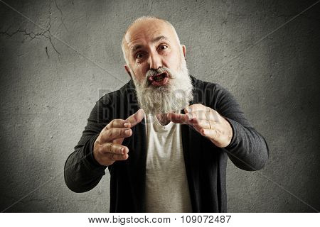 emotional bearded man screaming, stretching his hands to camera and want to smother someone over grey wall