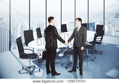 Business Partners Shake Hands In Modern Conference Room