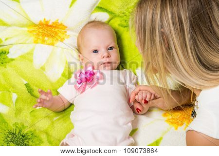 The Two-month Baby Lying On The Bed, Sitting Next To Mom