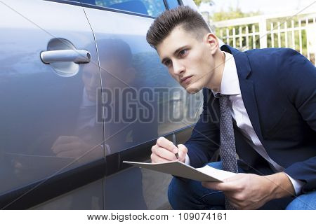 beautiful young insurance agent watching car damaged.