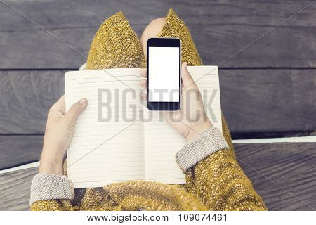 Girl With Blank Cell Phone Screen And Blank Diary On Wooden Bench, Mock Up