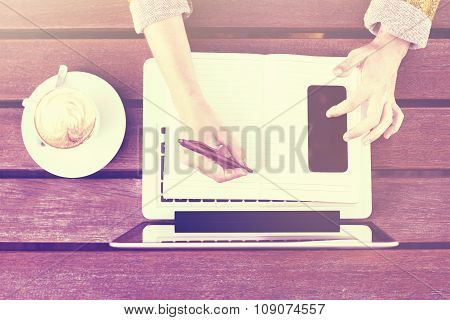 Girl Writing In Blank Diary With Cell Phone And Cup Of Coffee On Wooden Table