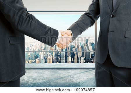 Businessmen Shake Hands At City Background