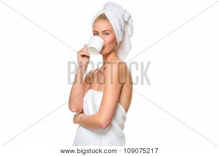 Young attractive woman with blue eyes in towel drinks