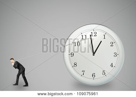 Stop Timing Concept With Businessman Trying To Stop The Time By Rope