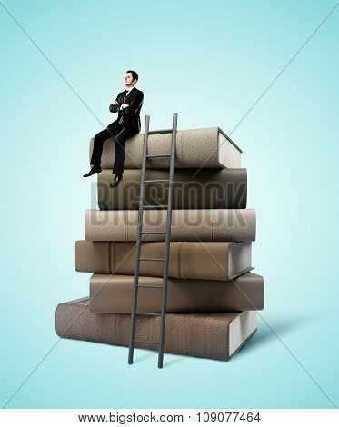 Man Sitting On Stack Of Books