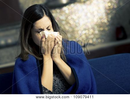 Sick young woman is coughing and blowing