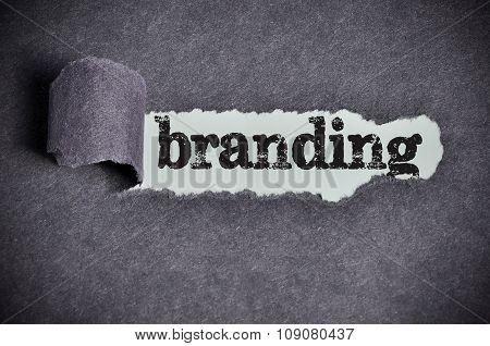 Branding Word Under Torn Black Sugar Paper