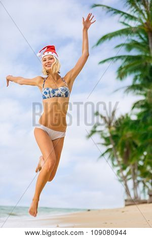 Young Blonde Woman In Bikini And Christmas Santa Hat Jumping On The Beach