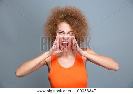 Portrait of angry furious mad young curly screaming woman in orange top isolated on gray background