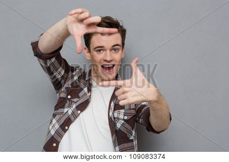 Joyful content cheerful excited handsome young man in checkered shirt making frame with fingers in front of his face