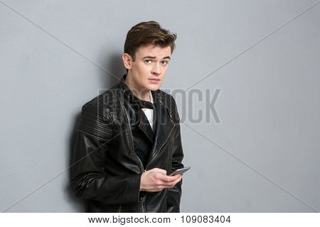 Portrait of a young man in leather jacket holding smartphone and looking at camera over gray background