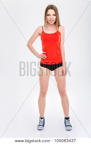 Happy cheerful pleased joyful pretty content girl in red top and black shorts standing on white background