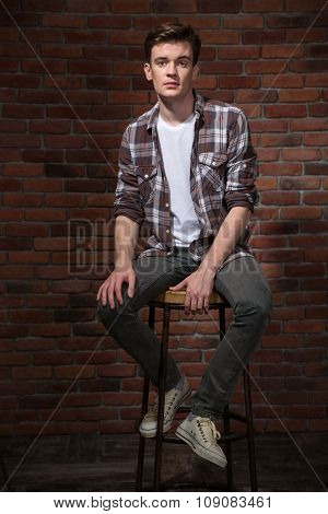 Confident handsome pensive modern young guy in plaid shirt sitting on bar chair