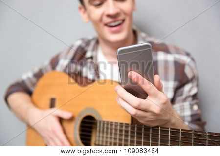 Cropped image of a man with guitar using smartphone. Focus on smartphone
