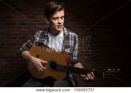 Handsome concentrated serious pensive young man in plaid shirt playing acoustic guitar and singing