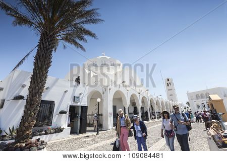 Tourists Walking At The Streets Of Santorini Island, Aegean Sea In Greece. The Most Famous Island In