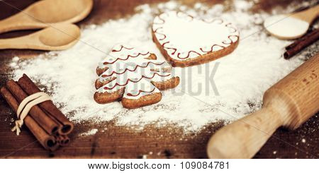 Christmas background  with gingerbread cookies, spices and flour over wooden background close up